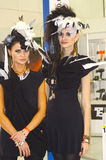 黑礼服的Intercharm XXI国际香料厂和化妆用品陈列两年轻美丽的妇女发光 库存图片