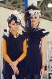 黑礼服的Intercharm XXI国际香料厂和化妆用品陈列两年轻美丽的妇女 免版税库存图片