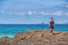 礼服立场的妇女在海的一块石头 免版税库存照片
