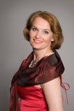 礼服红色微笑的妇女 免版税图库摄影