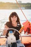 礼服航行豪华游艇的年轻美丽的微笑的女孩在有携带无线电话的在手上,日落海 图库摄影