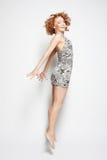 礼服跳跃的年轻迷人的女性 图库摄影