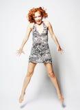 礼服跳跃的年轻迷人的女性 免版税图库摄影