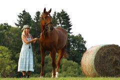礼服逗留的农夫妇女在干草捆附近的栗子马旁边 免版税库存照片