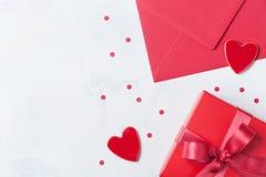 礼物、信封和红色心脏在白色桌上招呼的在情人节 平的位置 免版税图库摄影