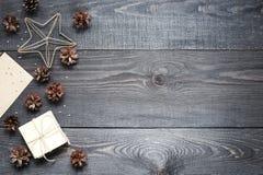 礼物、卡片、杉木锥体和cinnamonin在黑暗的木纹理 免版税库存图片