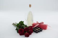 礼物、巧克力箱子、玫瑰和香槟瓶在白色背景 库存照片
