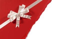 礼物丝带弓有不整洁被撕毁的红色纸背景,白色拷贝空间 免版税库存照片