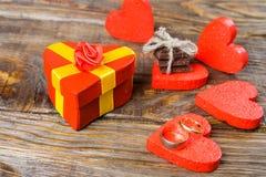 礼物包装在箱子以心脏的形式和栓与与一朵红色玫瑰的一条黄色丝带 装饰心脏围拢的礼物  免版税库存图片