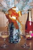 礼物包裹了在桌上的香宾与两块玻璃 库存图片
