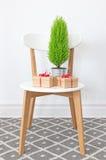 礼物和一点绿色树在一把白色椅子 图库摄影