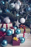 礼物和中看不中用的物品在一棵装饰的圣诞树下 图库摄影