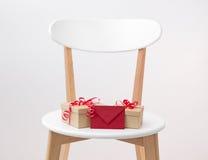 礼物和红色信封在一把木椅子 库存图片
