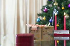 礼物在一个箱子、圣诞节云杉和蜡烛 库存照片