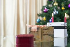 礼物在一个箱子、圣诞节云杉和蜡烛 免版税库存图片