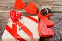 礼物在牛皮纸被包装并且栓与与一朵玫瑰的一条红色丝带在说谎垂饰以克洛的形式的中心 免版税库存照片