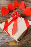 礼物在牛皮纸被包装并且栓与与一朵玫瑰的一条红色丝带在说谎垂饰以克洛的形式的中心 免版税库存图片