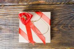 礼物在牛皮纸被包装并且栓与与一朵玫瑰的一条红色丝带在说谎垂饰以克洛的形式的中心 库存照片