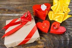 礼物在牛皮纸被包装并且栓与与一朵玫瑰的一条红色丝带在说谎垂饰以克洛的形式的中心 库存图片