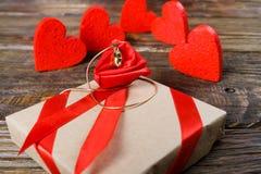 礼物在牛皮纸被包装并且栓与与一朵玫瑰的一条红色丝带在说谎垂饰的中心 免版税图库摄影