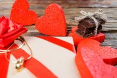 礼物在牛皮纸被包装,并且栓与一条红色丝带上升了 在一个的装饰心脏围拢的礼物婚戒打开 图库摄影