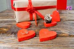 礼物在牛皮纸被包装,并且栓与一条红色丝带上升了 装饰心脏围拢的礼物一是一个婚戒与 免版税库存照片