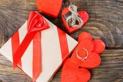 礼物在牛皮纸被包装,并且栓与一条红色丝带上升了 装饰心脏围拢的礼物一是婚戒 库存照片