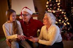 给礼物孙女的祖父母在圣诞前夕 库存图片