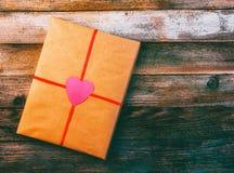 礼物对圣洁华伦泰的天包装纸的栓与与心脏的一条红色丝带在木减速火箭的难看的东西背景wi 免版税库存照片