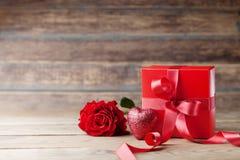 礼物或当前箱子、心脏和玫瑰色花在木土气桌上 母亲或情人节贺卡 复制文本的空间 库存图片
