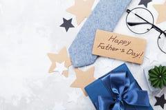 礼物或当前箱子、纸标记与愉快的父亲节,镜片和领带在白色台式视图 平的位置构成 免版税库存照片