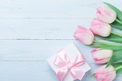 礼物或当前箱子和桃红色郁金香在蓝色木台式视图开花 贺卡为妇女或母亲节 平的位置 免版税库存图片