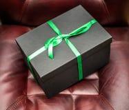 礼物或礼物盒在皮椅人的 库存图片