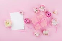 礼物或礼物,纸空白和美丽的花在桃红色书桌上从上面婚姻的大模型或贺卡的在妇女天 免版税库存图片