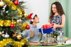给礼物的夫妇在圣诞晚餐 库存照片