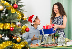 给礼物的夫妇在圣诞晚餐 免版税库存图片