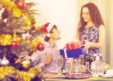 给礼物的夫妇在圣诞晚餐 免版税图库摄影