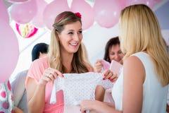 给礼物的妇女婴儿送礼会的怀孕的朋友 免版税库存照片