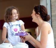 给礼物的小美丽的俏丽的女孩她愉快的母亲 免版税图库摄影