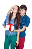 给礼物的愉快的人他的女朋友 在白色背景隔绝的愉快的年轻美好的夫妇 免版税库存照片