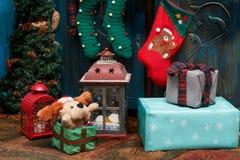 礼物盒、灯、红色起动、绿色长袜在地毯在蓝色老衣橱附近和小冷杉 免版税库存照片