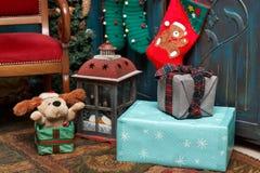 礼物盒、灯、红色起动、绿色长袜在地毯在蓝色老衣橱附近和棕色椅子 库存照片
