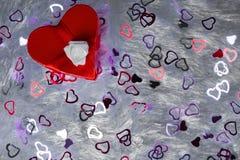 礼物盒以心脏的形式和栓与与弓的一条红色丝带以玫瑰的形式在散布的枕头伪造品毛皮说谎 免版税库存图片