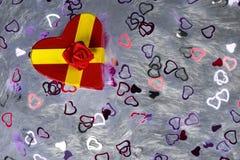 礼物盒以心脏的形式和栓与与弓的一条红色丝带以玫瑰的形式在散布的枕头伪造品毛皮说谎 免版税库存照片