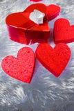 礼物盒以心脏的形式和栓与与弓的一条红色丝带以玫瑰的形式在枕头虚假毛皮周围说谎 免版税库存图片