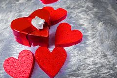 礼物盒以心脏的形式和栓与与弓的一条红色丝带以玫瑰的形式在枕头虚假毛皮周围说谎 库存图片