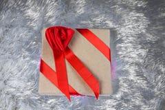 礼物盒包装在纸和栓与与弓的一条红色丝带以玫瑰的形式在枕头伪造品毛皮说谎 免版税库存照片