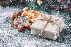 礼物盒包裹了亚麻布和装饰用绳子,黄麻,在棕色葡萄酒木板背景的圣诞节装饰 画 免版税库存图片