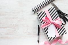 礼物盒和包装用材料在白色木老背景 被栓的问候笔记  图库摄影