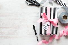 礼物盒和包装用材料在白色木老背景 被栓的问候笔记  库存照片
